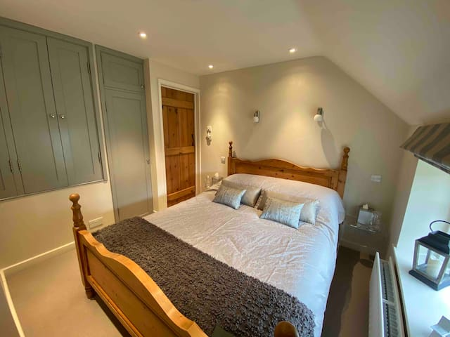 Extremely comfortable double bed,  and overlooking the owner's walled vegetable garden . Plenty of hanging and other storage. A very quiet and peaceful  and tasteful retreat.