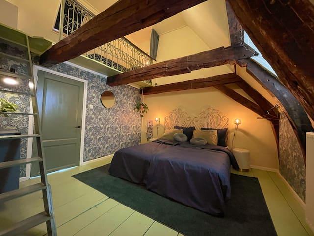 Dit is de prachtige slaapkamer boven! Kijk die karakteristieke gebinten. Wat combineert dat goed met het behang in art-deco stijl en de groene en gele tinten, voor een chic, natuurlijk en zomers gevoel.