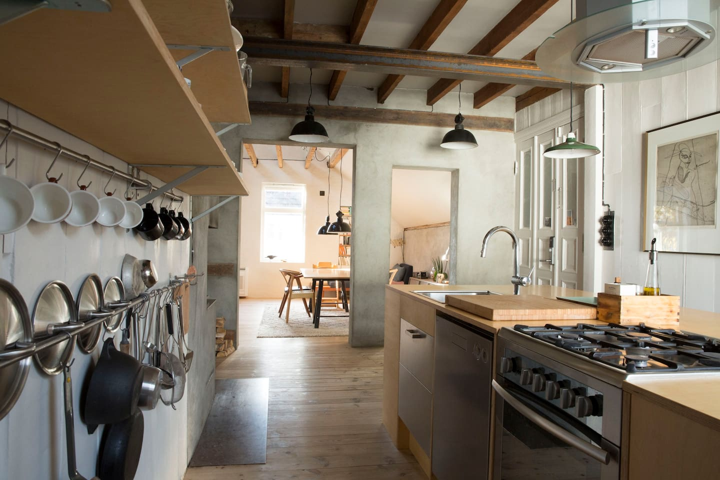Open and spacious kitchen with gas stove and electrical grill. Designed by ourselves, combining one of the first Danish hand crafted 60`ies kitchens with plywood. The dining room ceiling is more than five metres at the highest point.