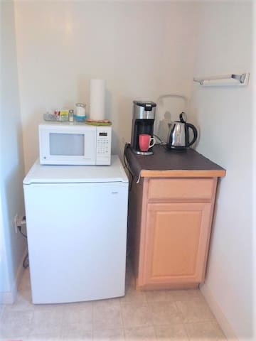 Kitchenette in guest area has cabinet and fridge, light food preparation appliances, and dishes.