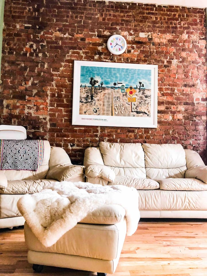 Historic exposed brick and Contemporary art collection accentuate the most comfortable Natuzzi Italian leather furniture and an alpaca covered ottoman in a shared common area. It's a relaxing retreat after a long day in the city.