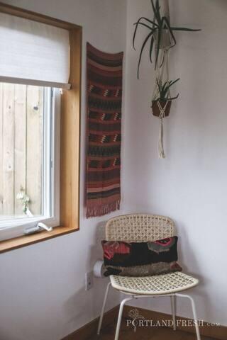 Tiny House window overlooking to garden. Macrame plant hanger by local artist Emily Katz. Photo by Christiann Koepke with Portland Fresh.