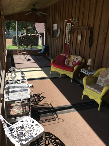 Screened in guest house porch overlooks pool and pasture.
