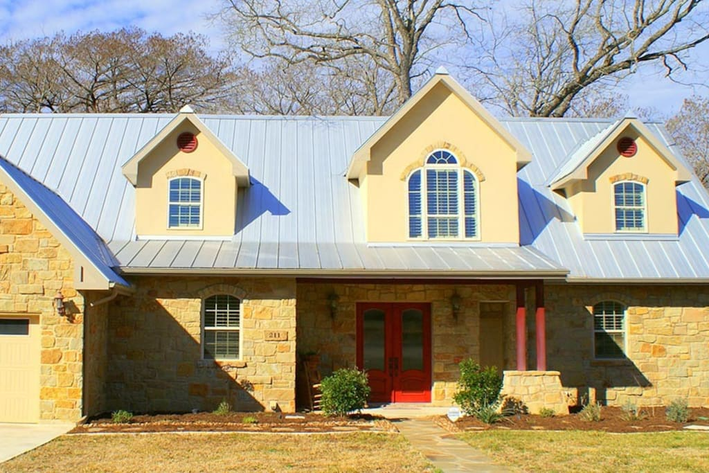 The front exterior. The private entrance to The Wimberley house is the door to the right of the red doors.