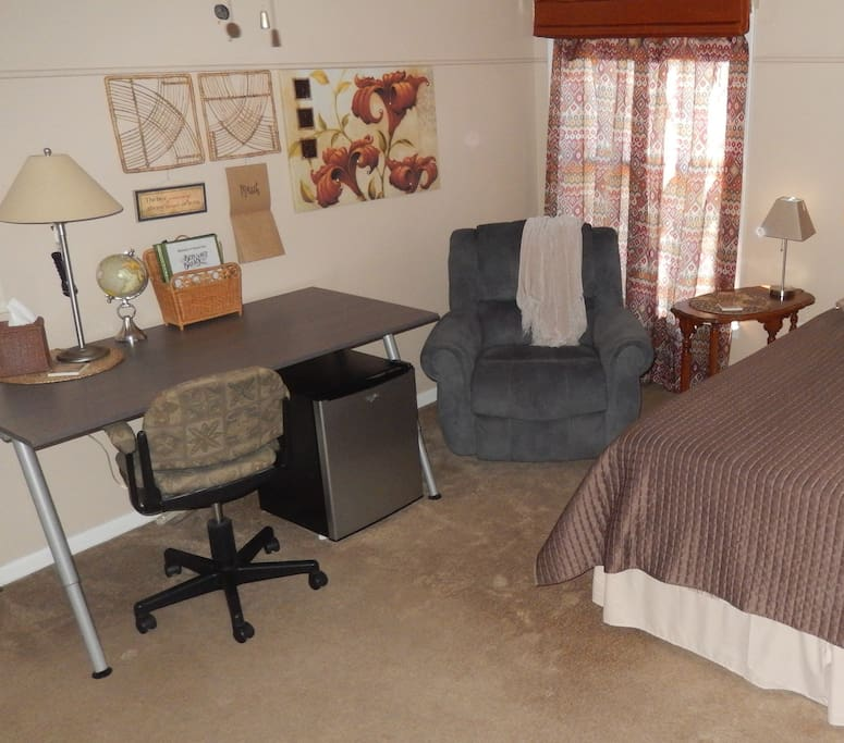 A recliner, a mini-fridge, a work space and a real comfortable bed... sweet!
