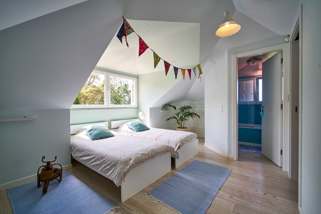 Upstairs room with two single bed and a fully equipped blue bathroom