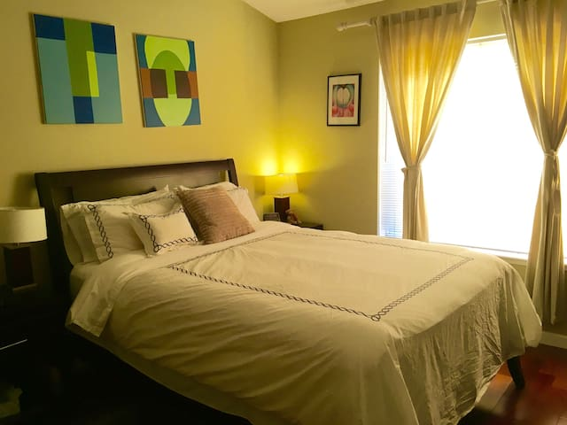 Master bedroom with queen bed, high ceiling