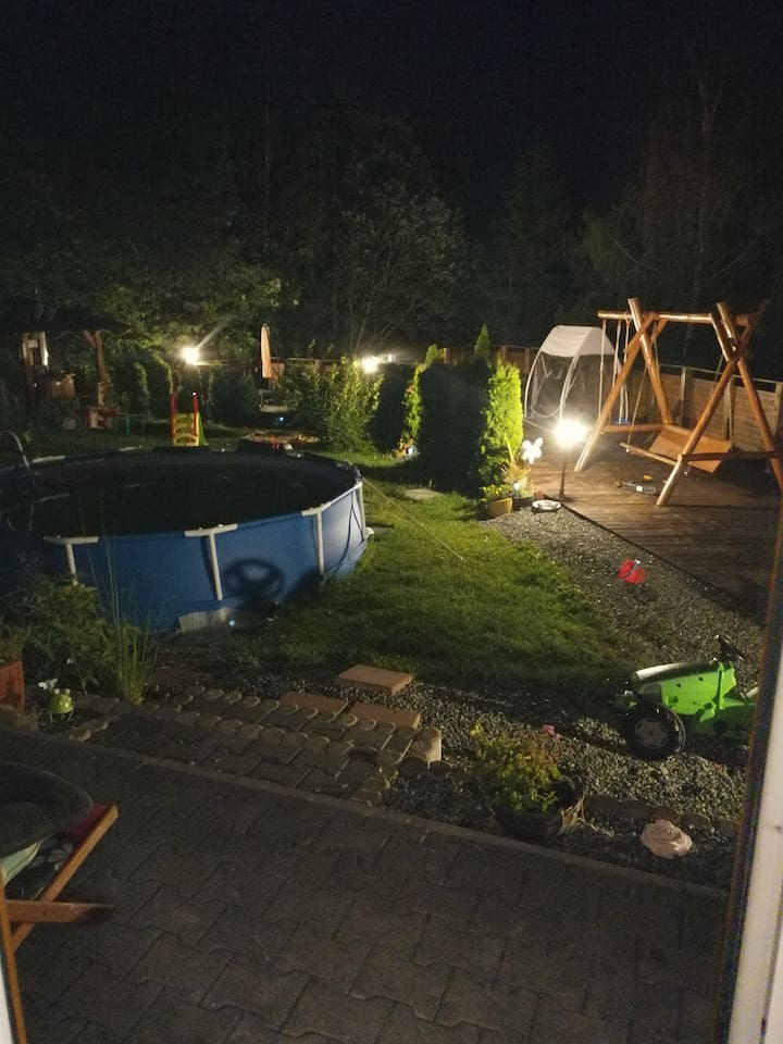 ogród w scenerii nocnej , oświetlony  i ogrodzony