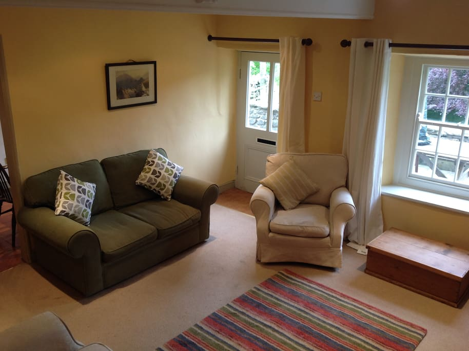 Warm, snug and well decorated sitting room with open fire and door leading out to terrace, lovely view, colour TV and DVD player.