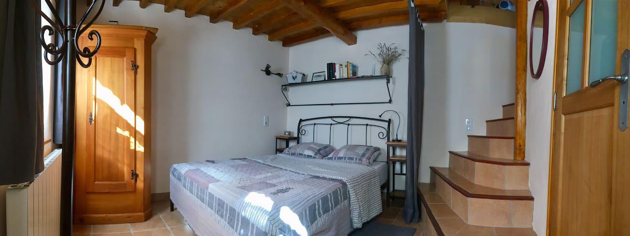 Chambre avec salle de bain et escaliers vers le salon et cuisine