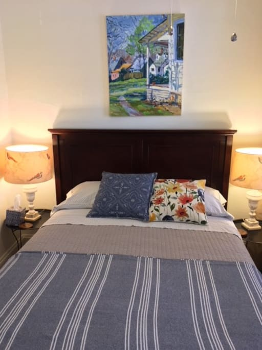 The room has two bedside lamps for reading, and original art by family and friends on the walls.
