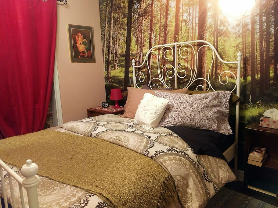 This brand new double bed is made up with a duvet, four pillows (of varying firmness) and fresh linens in fun colours set in front of a photo mural of an old growth forest.