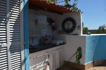 cocina con gas, microondas, utensilios para cocinar, vajilla y vasos, además de  nevera en el solarium
