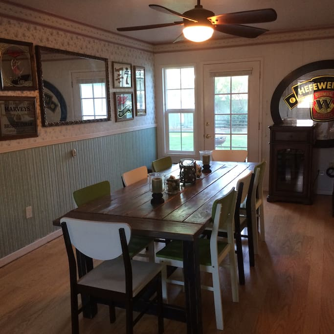 Barn table, floral walls, and vintage beer signs give the dining room a fun and cozy country feel.