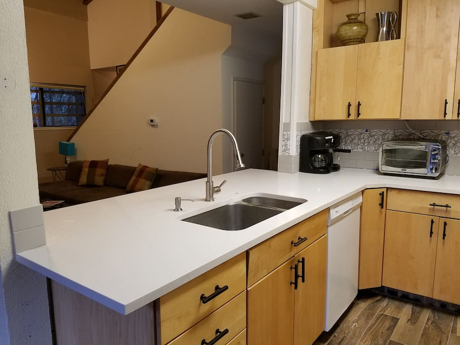 Quartz counter top opens to bar seating and the living room.