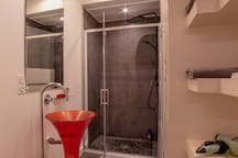 Large Italian style shower that fits 2 guests, washing machine, dryer, sink and large mirror.