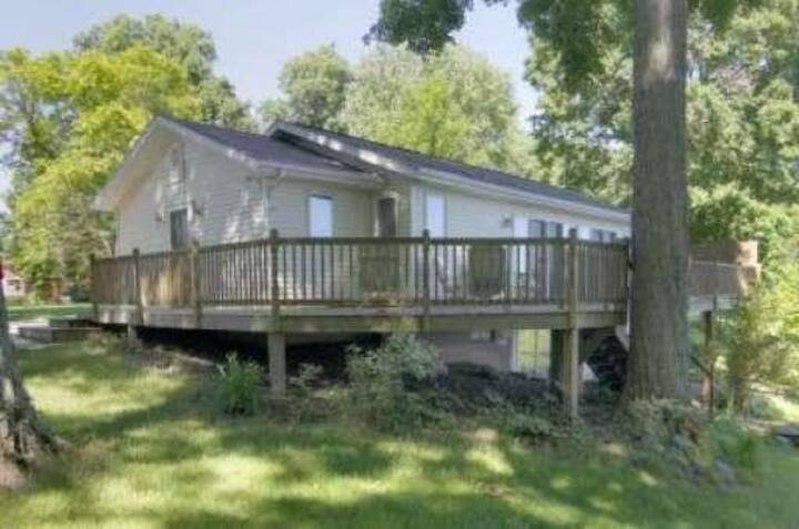 Miner Lake: Enjoy life on the lake from this waterfront home with expansive deck, beach, fire pit, boat dock, and more!