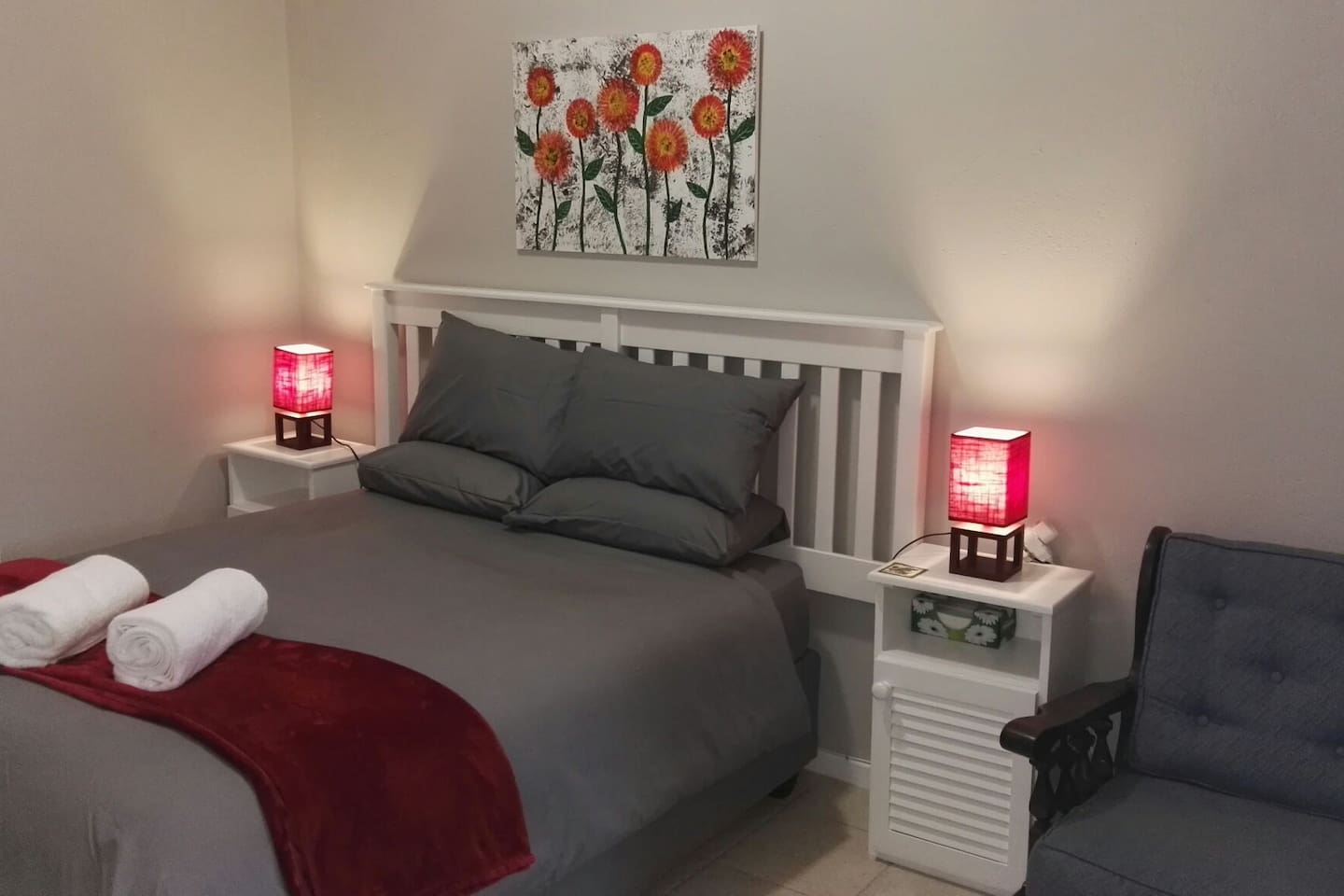 Bedroom, Queen size bed with bedding, Bedside tables with bedside lamps and towels.