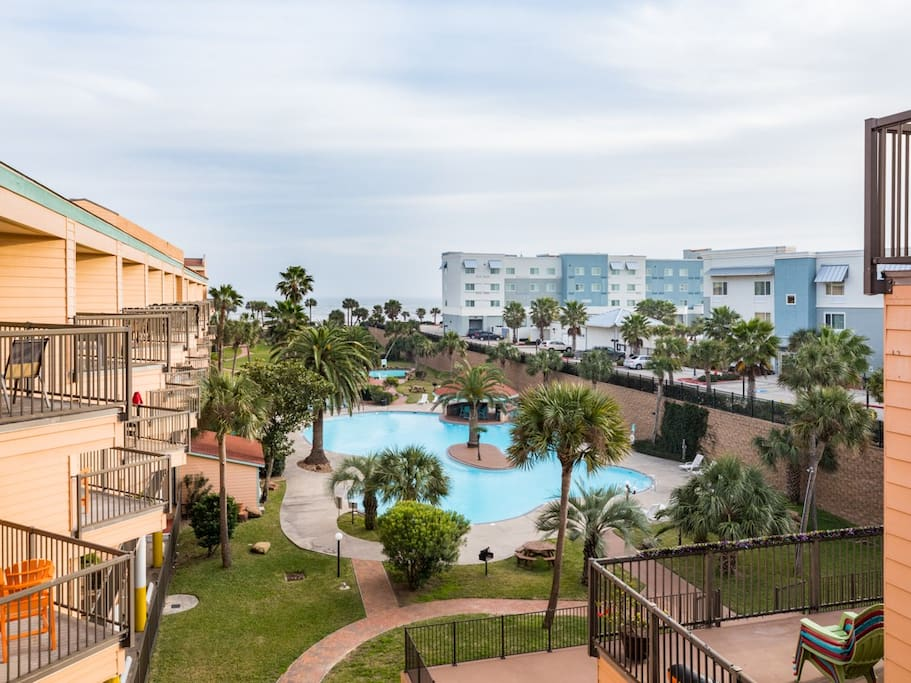 The resort boasts a huge pool with trees and lawn surrounding.