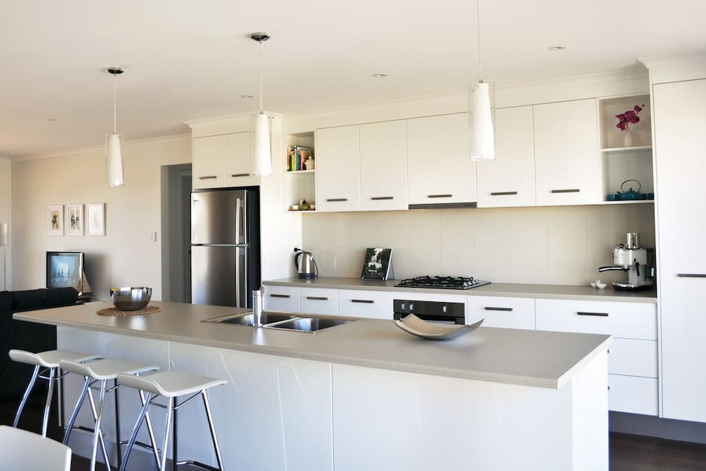 Modern fully equipped kitchen with electric oven and stove top, dishwasher and microwave.