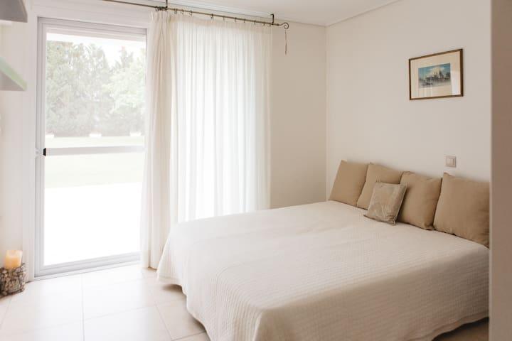 Η μία από τις δύο κρεβατοκάμαρες έχει δύο μονά κρεβάτια που ενώνονται και γίνονται ένα διπλό. Εχει μεγάλη μπαλκονόπορτα που σε οδηγεί στην βεράντα και τον μεγάλο κήπο.