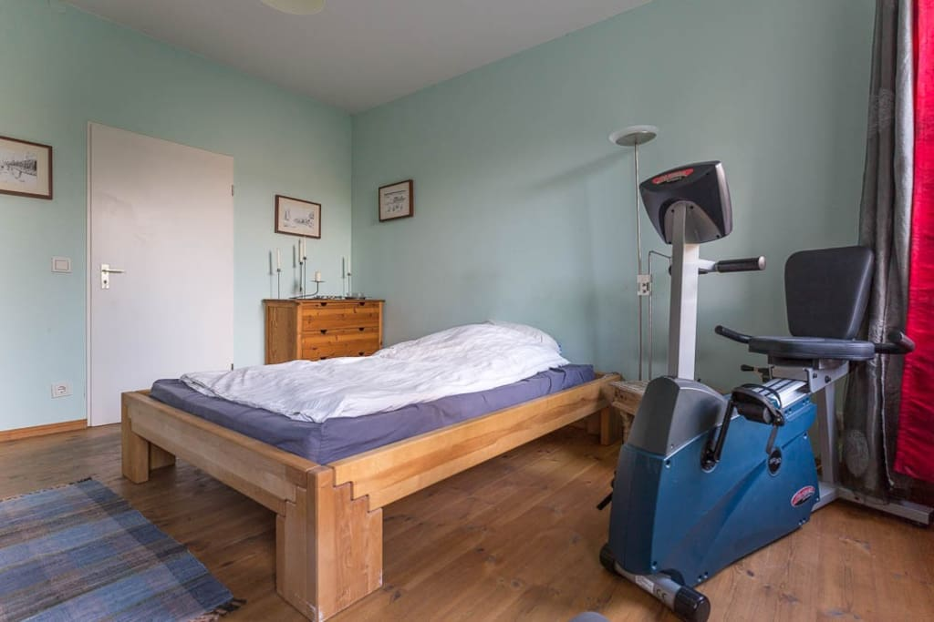 Schlafzimmer mit 140-Bett, Schreibtisch, Fahrradergometer und TV