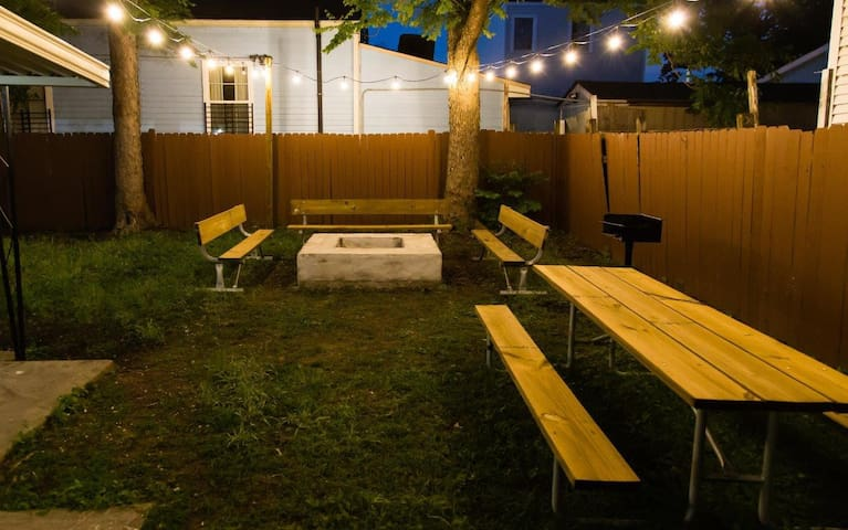 Outdoor fire pit with barbecue, picnic table and string lights