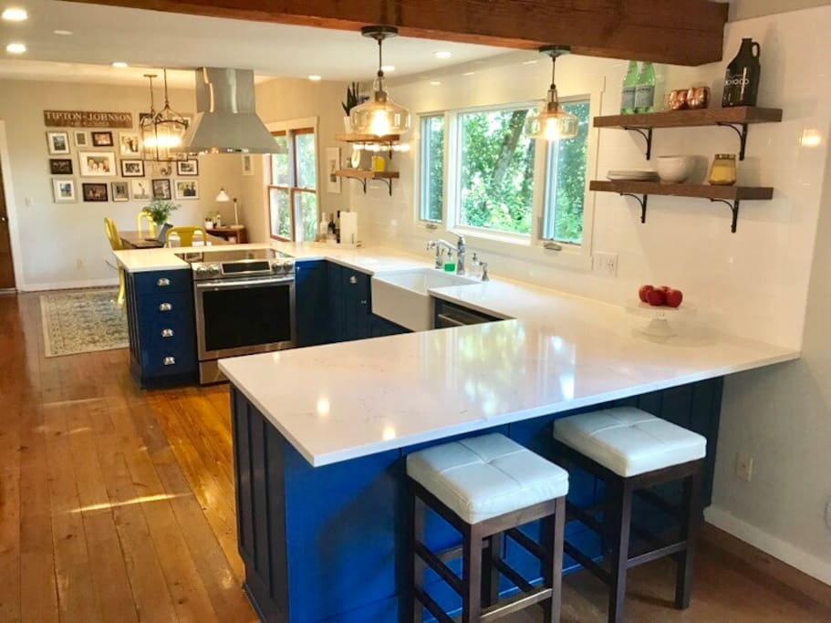 Newly renovated kitchen is the heart of the house; centrally located, with bar seating on both sides, lots of windows, make it a functional , social and bright space.