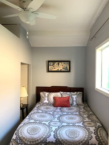 The path between the bed and closet is snug. Open closet space for your luggage storage and to hang clothes. Large ceiling fan.