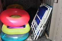 Back yard storage with toys, boogie boards, umbrellas, coolers, chairs and more.