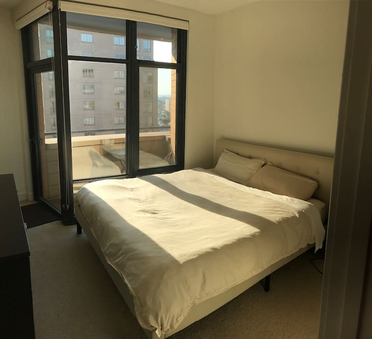 Beautiful sunny bedroom with floor to ceiling windows and balcony!