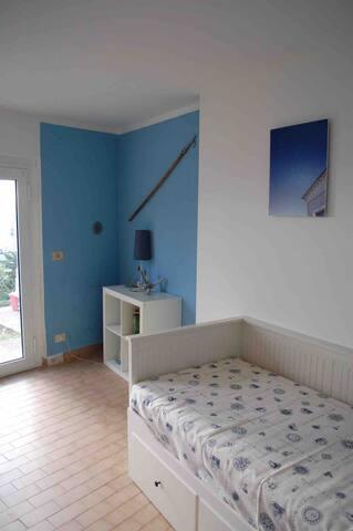 Schlafzimmer 4 mit Blick in den Garten und auf das Meer