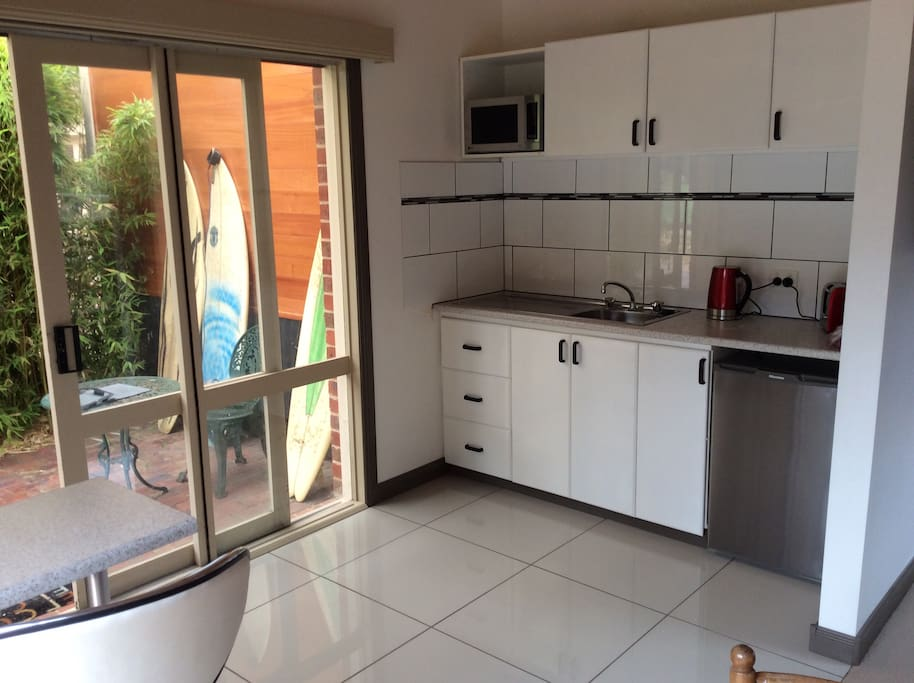 Open plan kitchen with microwave and bar fridge