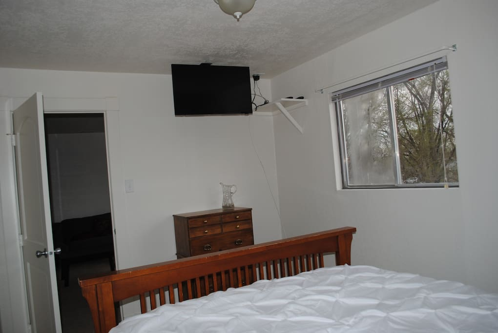 Queen bed with mounted TV and attached  bathroom