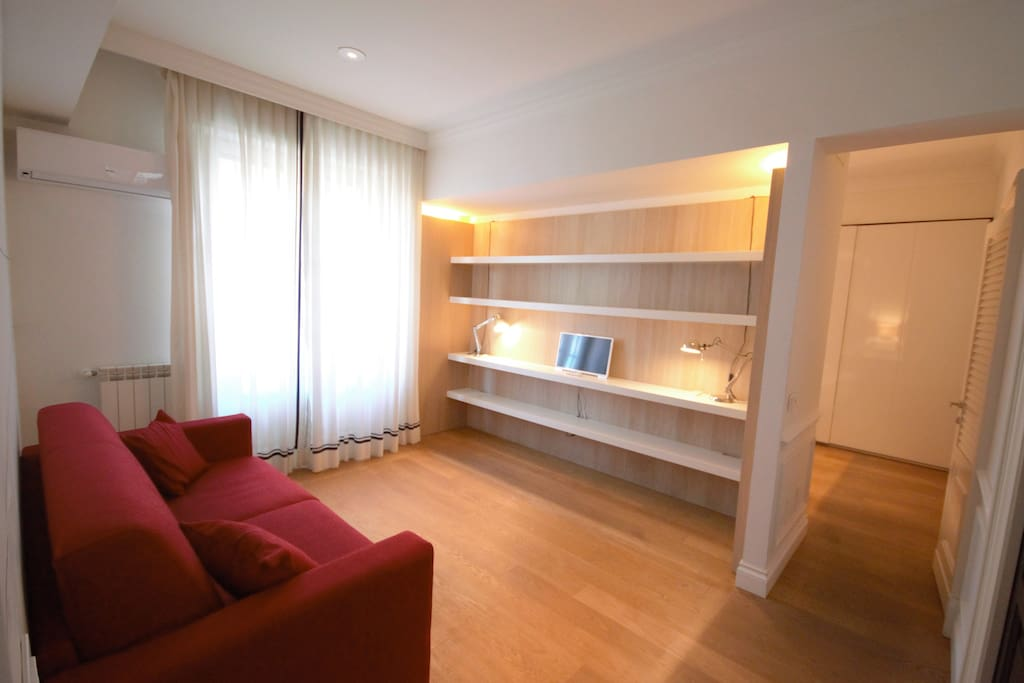 Beautiful living area with double sofa bed, window, TV, Air Conditioning. All the apartment has an elegant wooden floor.