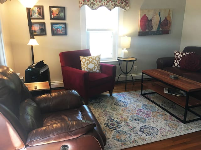 Big soft recliner, comfy chair with ottoman and leather couch in the living room.