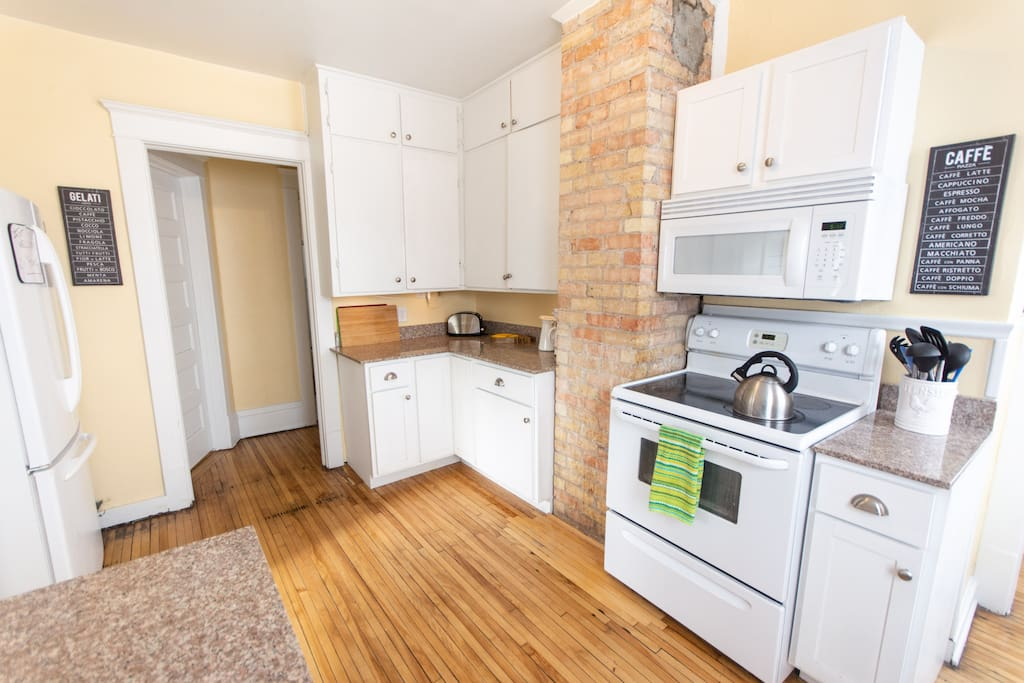 Kitchen with exposed brick, clean appliances for your use, and cabinets stocked with baking and cooking dishes, as well as dining dishes and silverware.