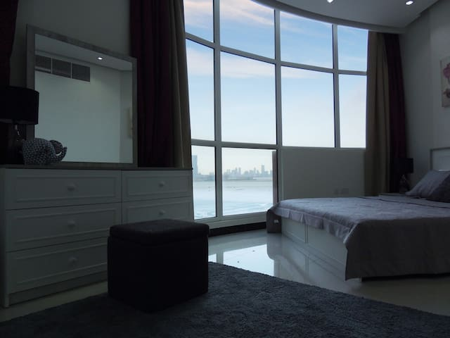 Master bedroom with a breathtaking panoramic sea view and city skyline.