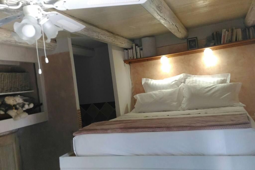 """le lit en hauteur, très """"cocon"""" avec ses oreiller confortables et l'ambiance du bois. Le ventilateur vous donnera un petit air doux et agréable."""