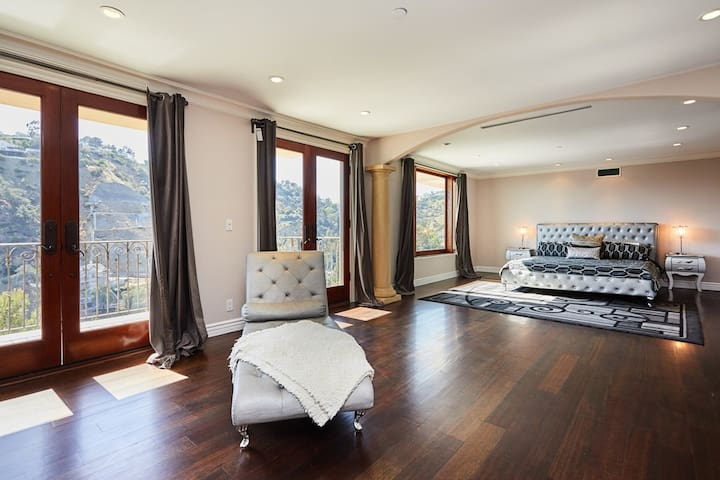 MASTER BEDROOM WITH A SITTING AREA, BALCONY AND VIEWS.
