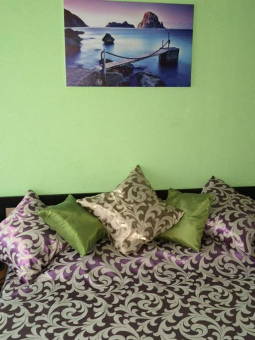 Большая двуспальная кровать и отдельный шкаф для одежды размещены в Зеленой спальне