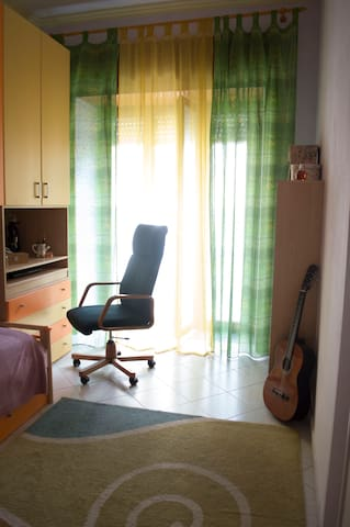 Small room with a single bed, desk, balcony and view on the garden.