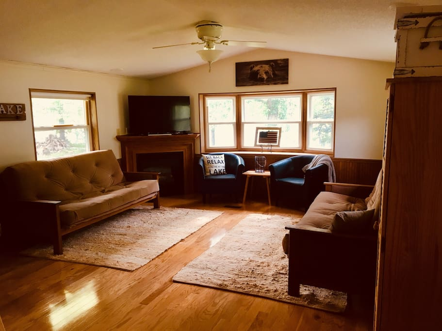 "Living room with two queen size futons, gas fireplace with 48"" Smart TV.  Looks out to lake!"