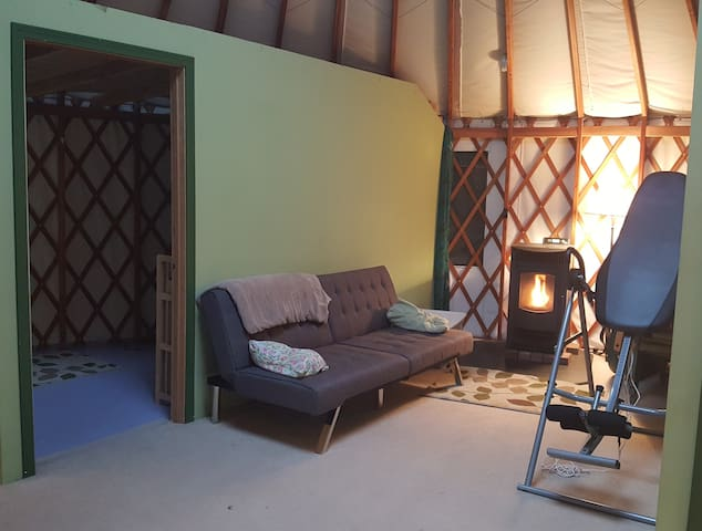 Pellet wood stove and extra futon for those rainy and cold days. To the right is an inversion table to stretch out your back after that long drive.