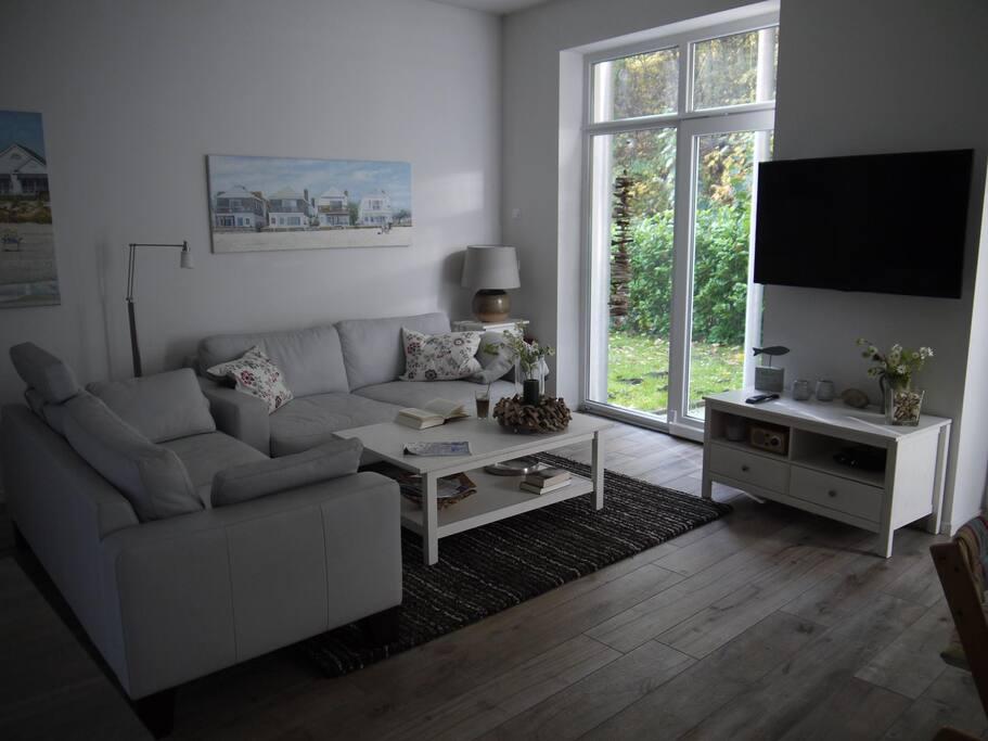 Wohnzimmerbereich mit Blick in den Garten und auf den Flachbildfernseher mit Satelliten-TV und DVD-Player