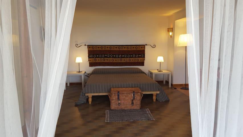 Camera matrimoniale a piano terra con grande porta-finesta che dà sul giardino . Annesso vi è il secondo bagno con doccia