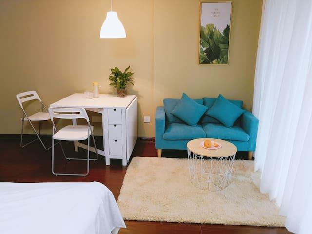 LOFT公寓设计,这是房间的会客区域,您可以和家人、朋友在这里休息聊天。房间里配置了白色的小桌子,可以用来用餐和书写。抹茶色的墙壁和绿色的植物给你带来最放松的体验。
