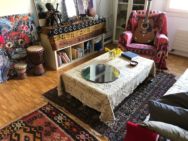 Another view of the cozy room, with art all over the place, carpets and objects from Morocco and Senegal, lots of books, a guitar and Djembé drums.