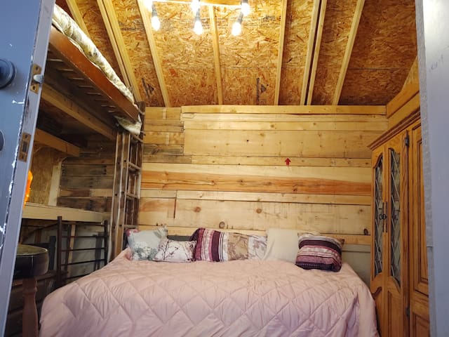 One of Two Beds. The other bed is a twin size loft bed up on the left.  The shiplap on the walls is from reclaimed wood cartons the Cabin came in.  There is a small wall unit to store your belongings.