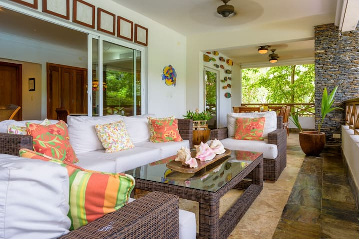 Balcony sitting area, overlooking the large pool and lush garden.